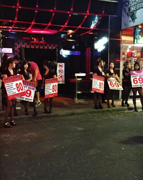 """Bar girls attract customers by advertising happy hour deals along Walking Street—Pattaya's red-light district. Upon entering a bar, customers are pressured to buy drinks for hostesses. """"Lady drinks"""" range in price, and a small portion of the money is given to the hostess. Image by Julia Boccagno. Thailand, 2015."""